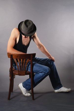 Man sitting on chair and lower his head in hat Stock Photo - 7642528