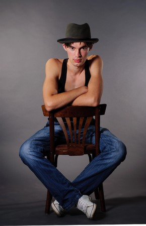 Man sitting on chair and lower his head in hat photo