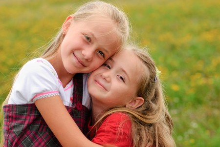 Two sisters hug one another outdoors, happy family Stock Photo - 7642583