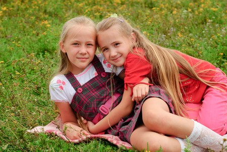 Two sisters hug one another outdoors, happy family photo