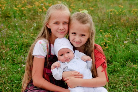 Two sisters hug one another and baby brother outdoors, happy family Stock Photo - 7642586