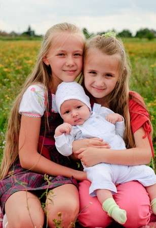 the three sisters: Two sisters hug one another and baby brother outdoors, happy family Stock Photo