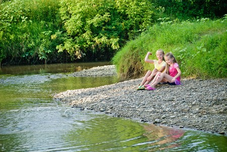 Two sisters throw stones into the river, have fun. photo