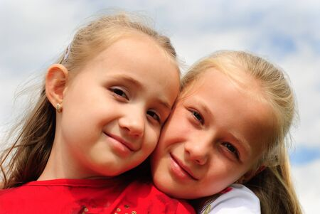 sibling: Two sisters hug one another outdoors, happy family. Close up faces. Stock Photo