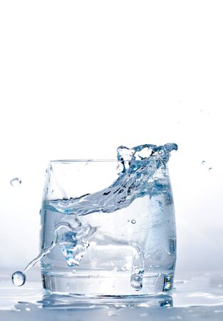 Throwed ice cube into the glass of water. Stock Photo - 7768594