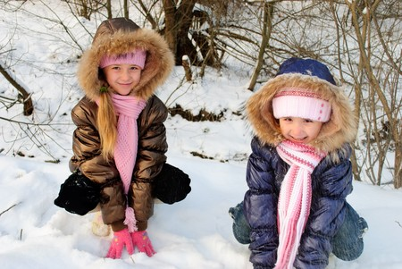 Two little sisters playing with snow outdoors photo