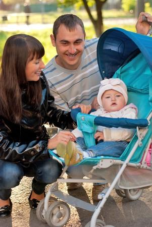 poussette: Famille heureuse en plein air - m�re, le p�re et dauther sont sourire en Landau