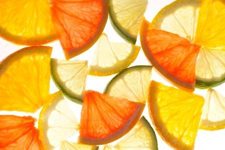 Citrus background from slices of orange, lemon, lime and grapefruit photo