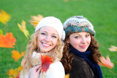 Two girl under the maple tree look on falling leaves. Close up faces photo