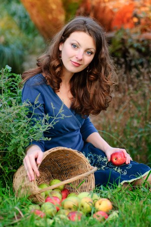 woman and apple crop in garden. Evening glow behind. Stock Photo - 8053341