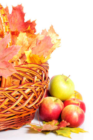 Apple and basket with maple leaves, scattering on white background. Symbol of autumn photo