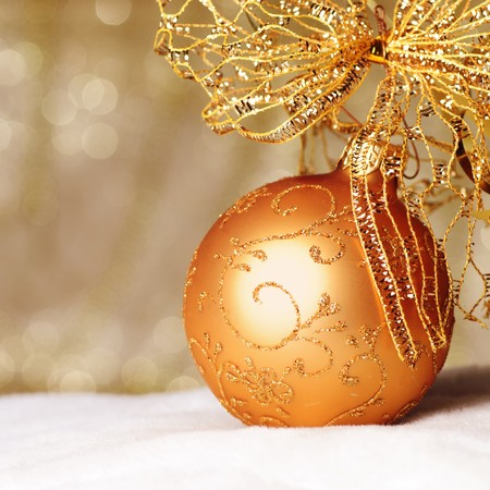 copysapce: Gold Christmas ball and bow ornament on white fur of defocused golden lights. Shallow DOF.