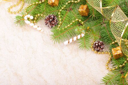 twirling: Gold Christmas ribbon, balls and beads on green pine branch