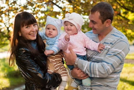 Happy family outdoor - mother, father, daughter and son are smiling Stock Photo - 8157924