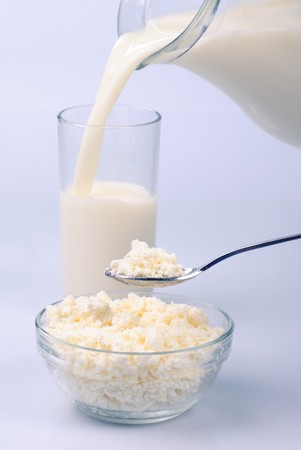 Milk in jug and glass and curds on white photo