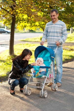 Happy family outdoor - mother, father and dauther are smiling in baby carriage photo