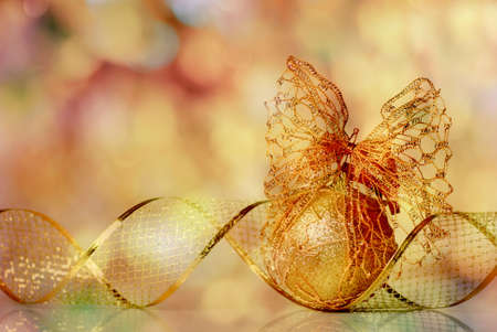 Gold Christmas ribbon ornament on background of defocused golden lights. Shallow DOF.  photo