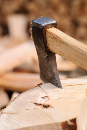 Firewood with axe and male hand. close up, shallow deep of field photo