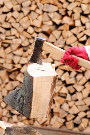 Firewood with axe and male hand. Stocking the fuel. photo