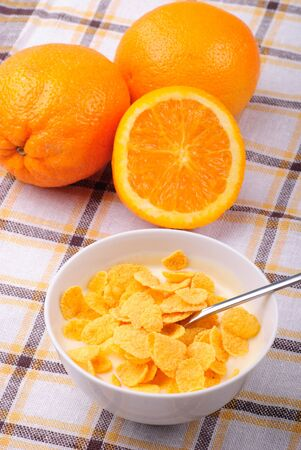 Breakfast from yoghurt with cornflakes and orange over tablecloth photo