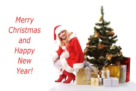 cheerful santa girl sitting on the gift under New-years tree. Copy text. Christmas greetings card photo
