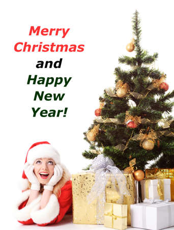 solemnity: cheerful santa girl lie near the gift and New-years tree. Copy text. Christmas greetings card