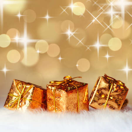 copysapce: Gold Christmas presents on white fur and background of defocused golden lights. Shallow DOF.