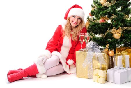 cheerful santa girl stand near the gift and New-years tree. Copy text. Christmas greetings card photo