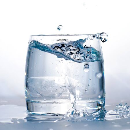 Throwed ice cube into the glass of water. Stock Photo - 8387695