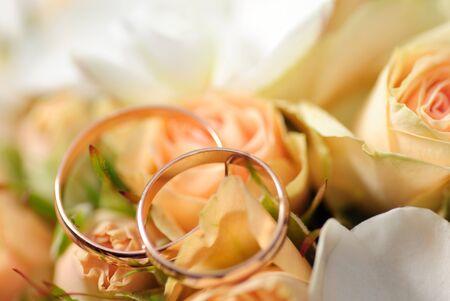 Anillos de oro en un ramo de rosas. DOF superficial, enfoque selectivo. Weddinf postal  Foto de archivo