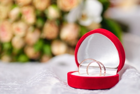 Gold rings on background of a bouquet of roses. Shallow DOF, selective focus photo
