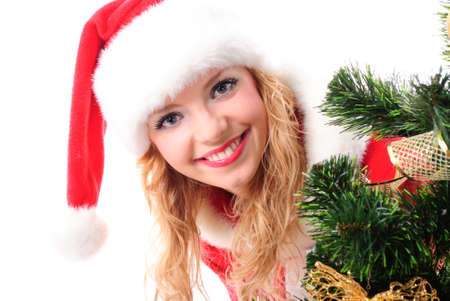 cheerful santa girl stand near the gift and New-year's tree. Copy text. Christmas greetings card Stock Photo - 8399806