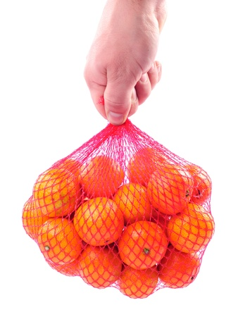 Hand holding a bag of tangerines isolated on white background. photo