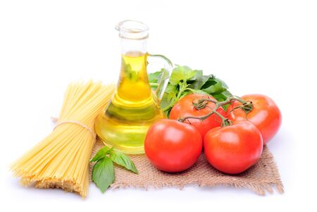 Spaghetti with tomatoes, olive oil and basil on a sacking isolated on white photo