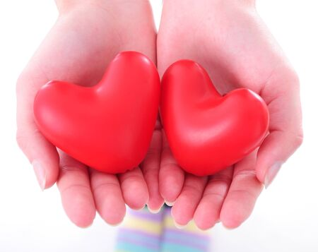 two red baloon hearts oin female hands  photo
