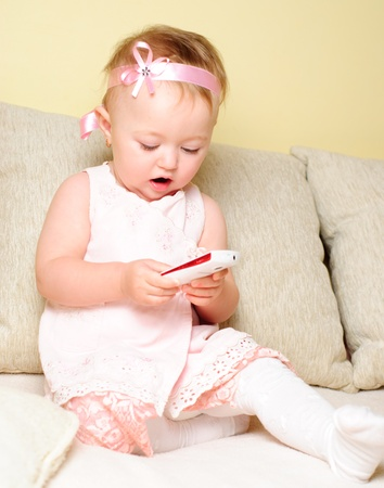 playing on divan: Little girl are sitting on the sofa and playing with mobile phone