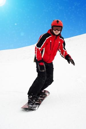 Man on snowboard skiin down on mountain. It is snowing photo
