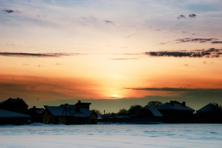 Rural winter landscape with sundown and houses under the snow.  photo