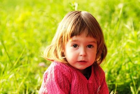 Little girl in garden, on green grass photo