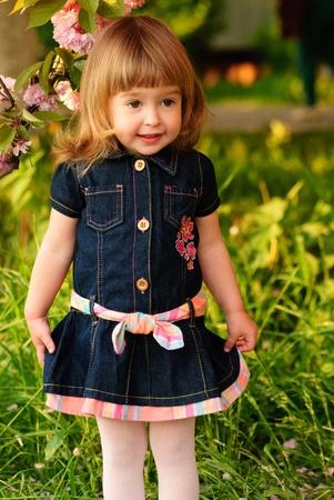 frock: Little girl in garden, under the sakura tree. Spring petals rain.