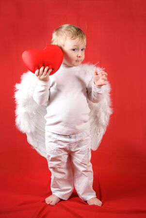 Little amour blond boy with red heart photo