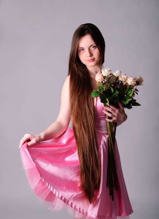 Woman in pink silk dress and roses in her hand photo