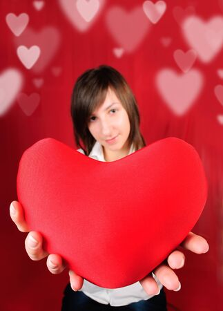 Teenage girl with red heart shape on red background Stock Photo - 8870019