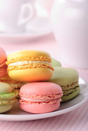 Pink, yellow, green macaroones on white plate close up photo