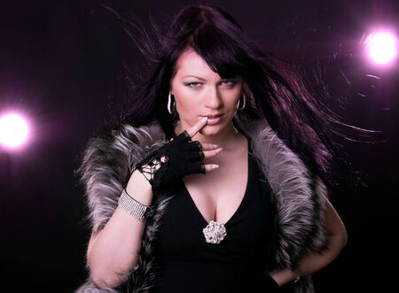Woman in fur coat on black backgound and magenta light photo