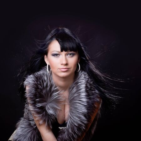 Woman in fur coat on black backgound Stock Photo - 9086971