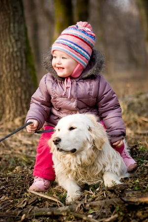 Girl with golden retriever are playing in the park photo