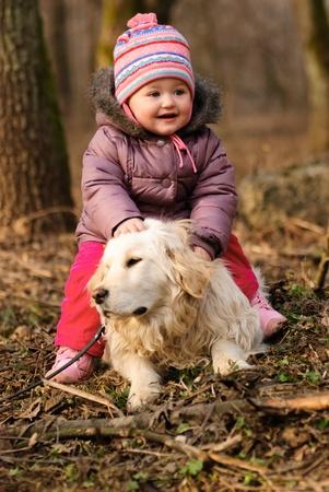 Niña con golden retriever están jugando en el Parque Foto de archivo