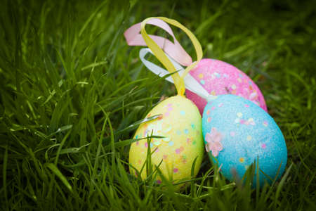 three colorfull easter eggs on green grass photo
