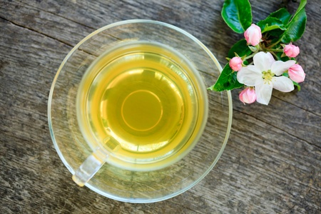Green tea in glass cup and flowers on wooden table photo